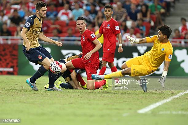 Jon Toral is tackled by goalkeeper Izwan Mahbud of Singapore Select XI during the Barclays Asia Trophy match between Arsenal and Singapore Select XI...