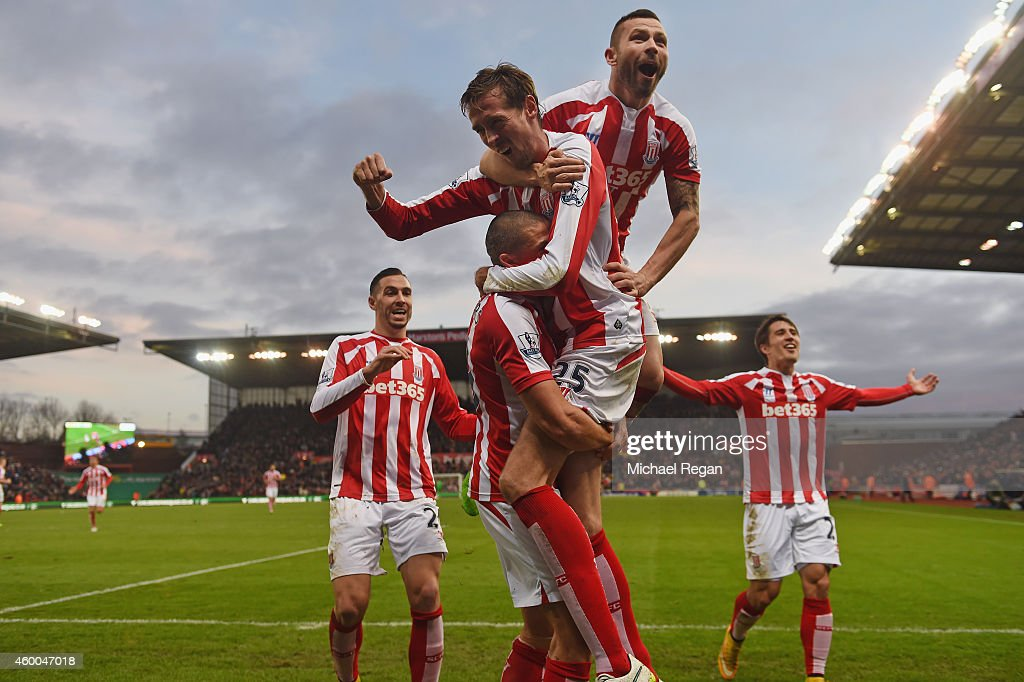 Jon Walters of Stoke is mobed by Phil Bardsley and Peter Crouch after scoring to make it 3-0 during the Barclays Premier League match between Stoke City and Arsenal at Britannia Stadium on December 6, 2014 in Stoke on Trent, England.