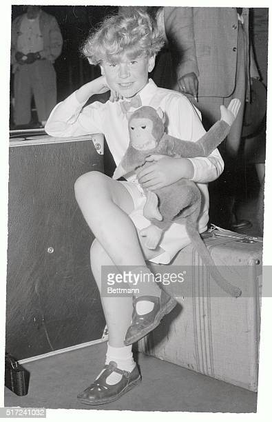 Jon Whiteley 9 1/2 year old movie star from Scotland holds a toy monkey as he waits for his baggage to clear customs after arriving in New York...