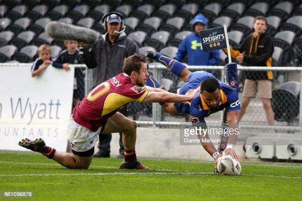 Jona Nareki of Otago dives over to score a try while tackled by Scott Eade of Southland during the round nine Mitre 10 Cup match between Otago and...