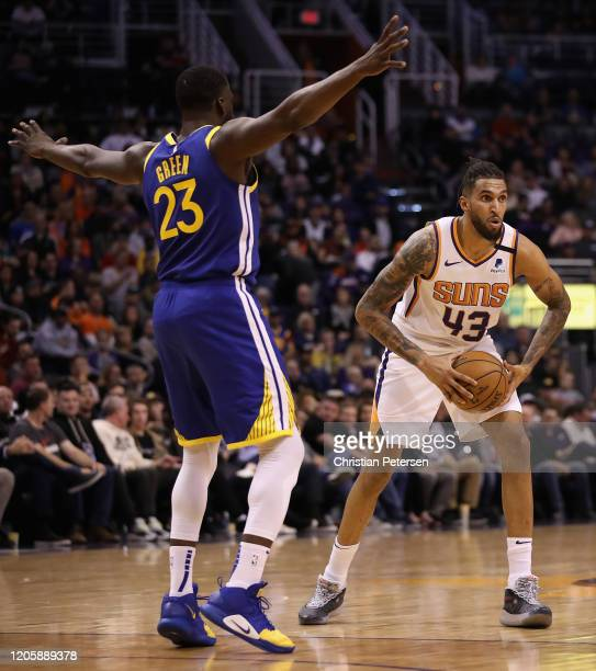 Jonah Bolden of the Phoenix Suns looks to pass defended by Draymond Green of the Golden State Warriors during the first half of the NBA game at...