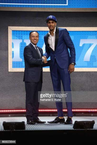 Jonah Bolden shakes hands with Deputy Commissioner Mark Tatum after being selected thirty sixth overall by the Philadelphia 76ers during the 2017 NBA...
