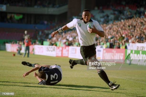Jonah Lomu of New Zealand goes round Scotland's Scott Hastings to score the first try during a Rugby World Cup match in Pretoria 11th June 1995 New...