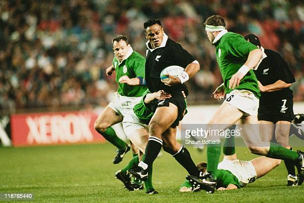 Jonah Lomu of New Zealand looks for support as he is tackled by Eric Elwood of Ireland during a Rugby World Cup pool stage match at Ellis Park...