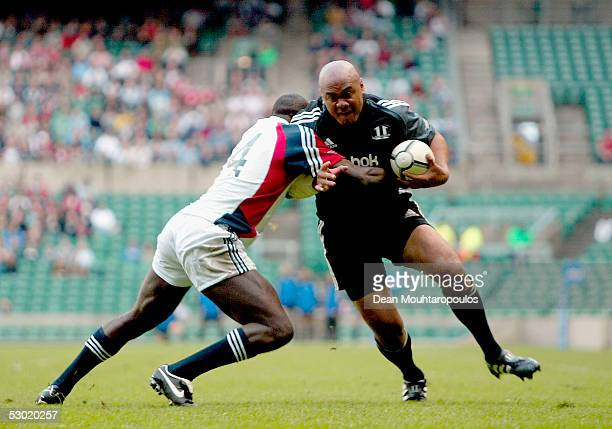 Jonah Lomu of Southern Hemishpere XV holds off the tackle from Ayoola Erinle of Northern Hemsiphere XV to score a try during the Martin Johnson...