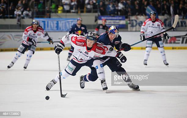 Jonah Miller of Berlin is challenged by Matt Smaby of EHC Muenchen during the DEL Ice Hockey match between EHC Muenchen and Eisbaeren Berlin on...