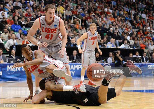 Jonah Travis of the Harvard Crimson is jumped on by Chad Adams of the New Mexico Lobos in after they go for a loose ball in the second half during...