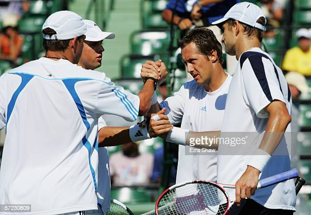 Jonas Bjorkman of Sweden and his partner Max Mirnyi of Belarus are congratulated by Mike and Bob Bryan after Bjorkman and Mirnyi won the men's...
