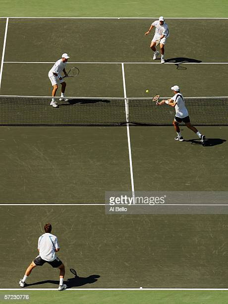 Jonas Bjorkman of Sweden and Max Mirnyi of Belarus return a shot to Mike and Bob Bryan in the men's doubles final at the Nasdaq100 Open at the Tennis...