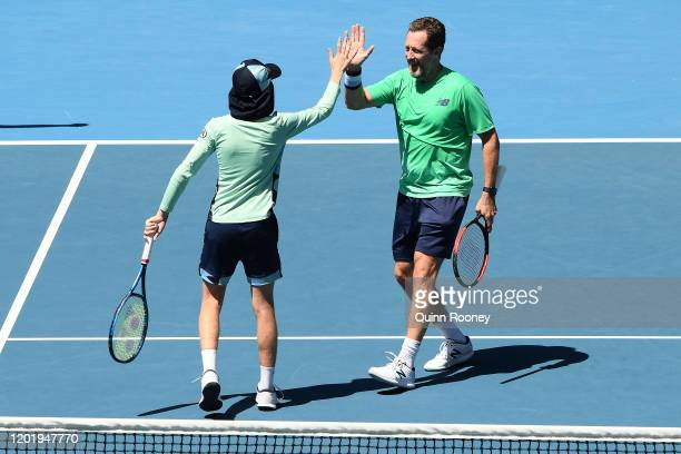 Jonas Bjorkman of Sweden celebrates with a ball kid during their Men's Legends Doubles match against Tommy Haas of Germany and Mark Philippoussis of...