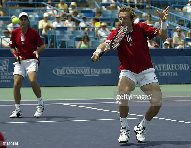 Jonas Bjorkman of Sweden returns a shot as doubles teammate Todd Woodbridge of Australia looks on during the Western and Southern Financial Group...