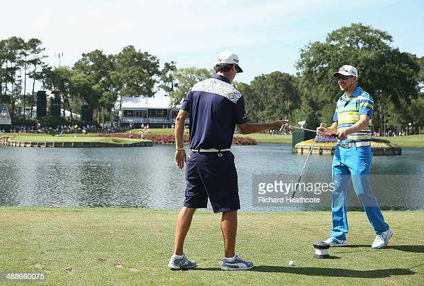 Jonas Blixt of Sweden gives his caddy a club to hit into the 17th green during a practice round ahead of THE PLAYERS Championship on The Stadium...