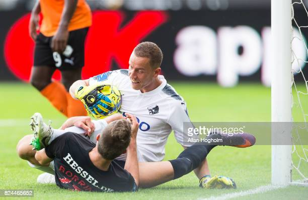 Jonas Borring of FC Midtjylland and Hannes Thor Halldorsson of Randers FC compete for the ball during the Danish Alka Superliga match between FC...