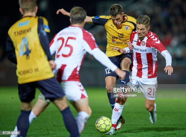 Jonas BrixDamborg of Hobro IK and Kasper Risgard of AaB Aalborg compete for the ball during the Danish Alka Superliga match between Hobro IK and AaB...