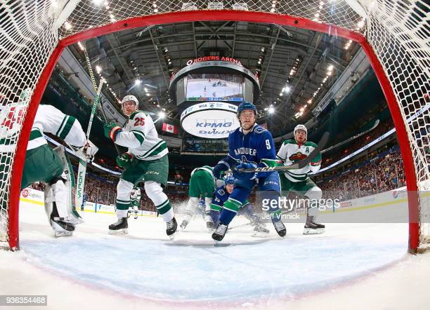 Jonas Brodin and Zach Parise of the Minnesota Wild and Brendan Leipsic of the Vancouver Canucks watch a loose puck during their NHL game at Rogers...