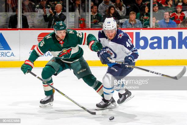 Jonas Brodin of the Minnesota Wild and Brendan Lemieux of the Winnipeg Jets skate to the puck during the game at the Xcel Energy Center on January 13...