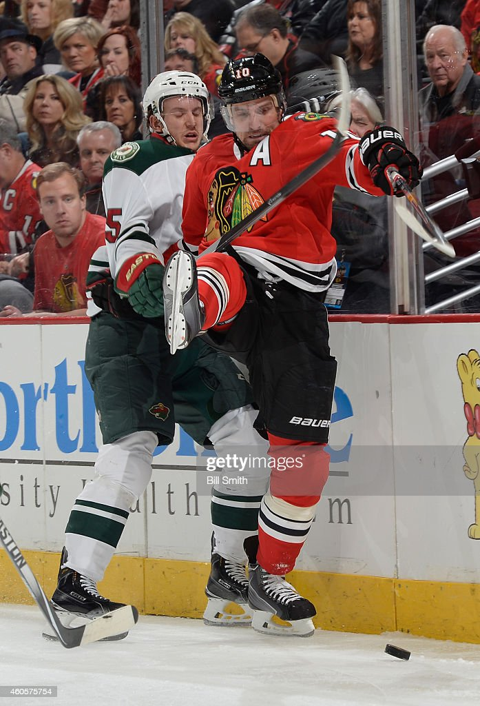 Jonas Brodin #25 of the Minnesota Wild and Patrick Sharp #10 of the Chicago Blackhawks get physical during the NHL game at the United Center on December 16, 2014 in Chicago, Illinois.