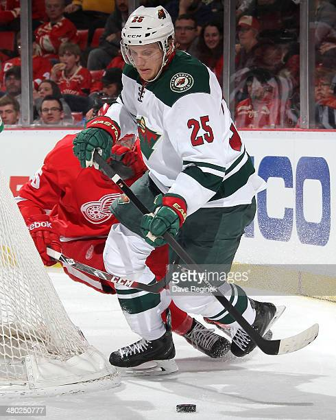 Jonas Brodin of the Minnesota Wild plays the puck as Cory Emmerton of the Detroit Red Wings pressures him behind the net during an NHL game on March...