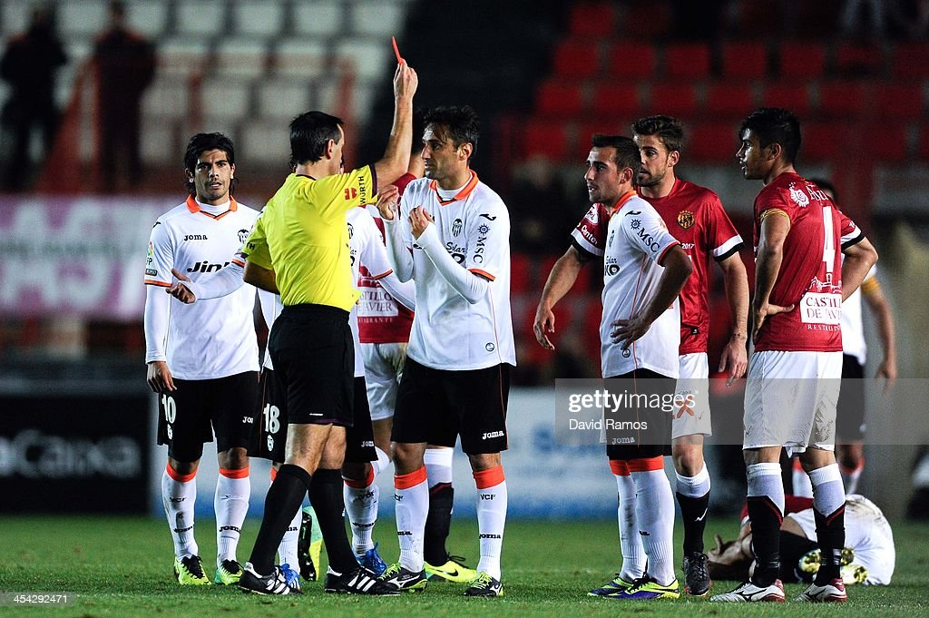 Jonas Goncalves (R) of Valencia CF is shown a red card by the referee Jose Antonio Teixeira during the Copa del Rey round of 32 match between Gimnastic de Tarragona and Valencia at Nou Stadi on December 8, 2013 in Tarragona, Spain.