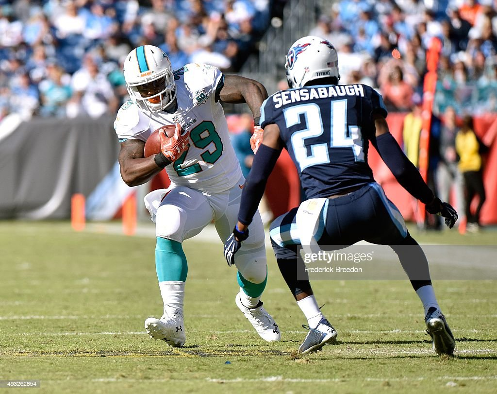 Jonas Gray #29 of the Miami Dolphins carries the ball against Coty Sensabaugh #24 of the Tennessee Titans during the second half of a game at Nissan Stadium on October 18, 2015 in Nashville, Tennessee.