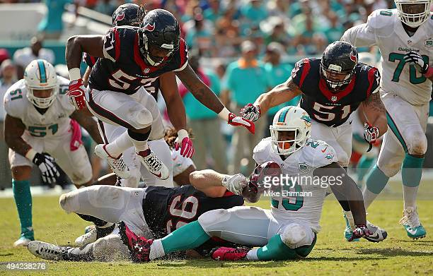 Jonas Gray of the Miami Dolphins is tackled by JJ Watt of the Houston Texans during a game against the Houston Texans at Sun Life Stadium on October...
