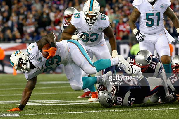 Jonas Gray of the Miami Dolphins is tackled during the second quarter against the New England Patriots at Gillette Stadium on October 29 2015 in...