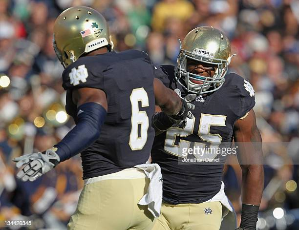 Jonas Gray of the Notre Dame Fighting Irish celebrates a touchdown run with Theo Riddick against the Navy Midshipmen at Notre Dame Stadium on October...