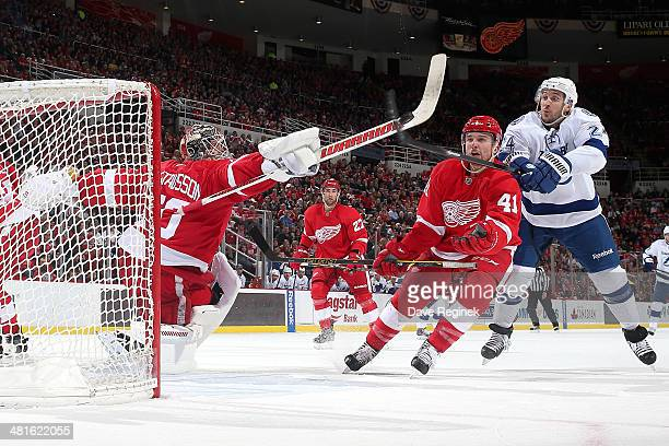 Jonas Gustavsson and Luke Glendening of the Detroit Red Wings battle for an airborne puck with Ryan Callahan of the Tampa Bay Lightning during an NHL...