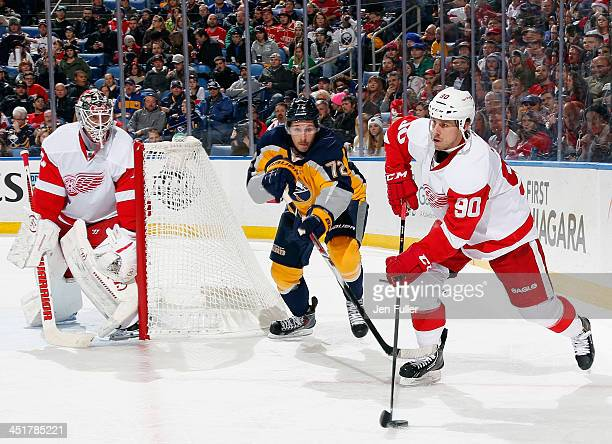 Jonas Gustavsson of the Detroit Red Wings defends the net as teammate Stephen Weiss carries the puck against Luke Adam of the Buffalo Sabres at First...
