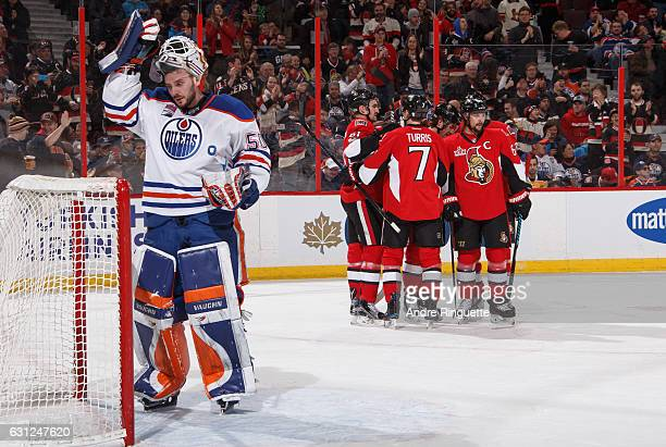 Jonas Gustavsson of the Edmonton Oilers adjusts his mask as Mike Hoffman of the Ottawa Senators celebrates his first period goal with teammates Mark...