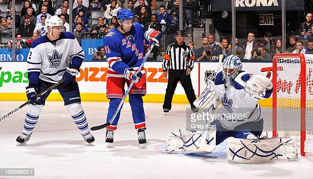 Jonas Gustavsson of the Toronto Maple Leafs makes a glove save as teammate Luke Schenn keeps an eye on Alexander Frolov the New York Rangers during...