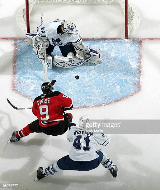 Jonas Gustavsson of the Toronto Maple Leafs makes a save as his teammate Nikolai Kuleman checks Zach Parise of the New Jersey Devils during their...