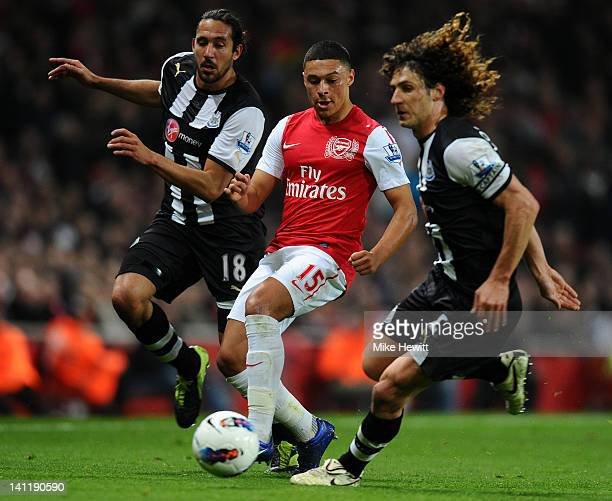 Jonas Gutierrez and Fabrizio Coloccini of Newcastle close down Alex OxladeChamberlain of Arsenal during the Barclays Premier League match between...