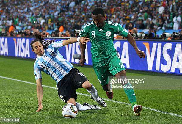 Jonas Gutierrez of Argentina tackles Yakubu Ayegbeni of Nigeria during the 2010 FIFA World Cup South Africa Group B match between Argentina and...