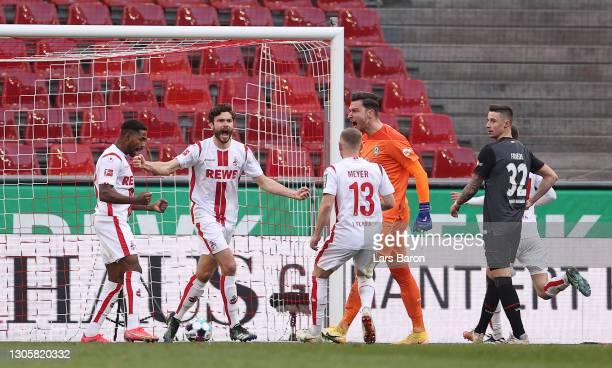 Jonas Hector of 1. FC Koeln celebrates after scoring their side's first goal as Jiri Pavlenka of SV Werder Bremen reacts during the Bundesliga match...