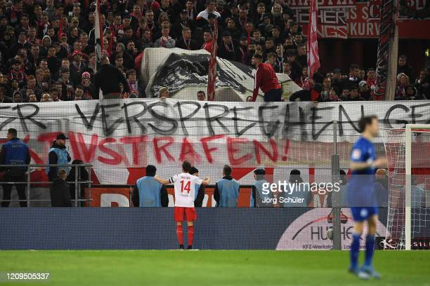 Jonas Hector of 1. FC Koeln reasons with fans as they display a banner during the Bundesliga match between 1. FC Koeln and FC Schalke 04 at...