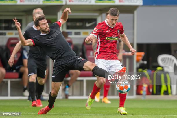 Jonas Hector of 1.FC Koeln and Roland Sallai of SC Freiburg battle for the ball during the Bundesliga match between Sport-Club Freiburg and 1. FC...