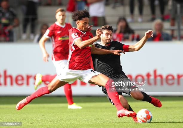 Jonas Hector of 1.FC Koeln is challenged by Kevin Schade of SC Freiburg during the Bundesliga match between Sport-Club Freiburg and 1. FC Köln at...