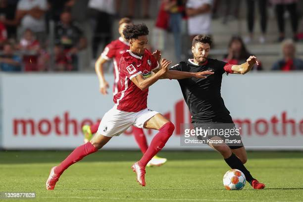 Jonas Hector of 1.FC Koeln is tackled by Kevin Schade of SC Freiburg during the Bundesliga match between Sport-Club Freiburg and 1. FC Köln at...