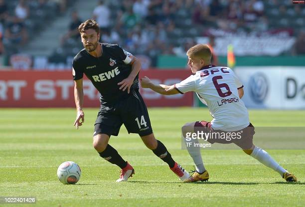 Jonas Hector of FC Koeln and Bjoern Lambach of BFC Dynamo battle for the ball during the DFB Cup first round match between BFC Dynamo and 1 FC Koeln...