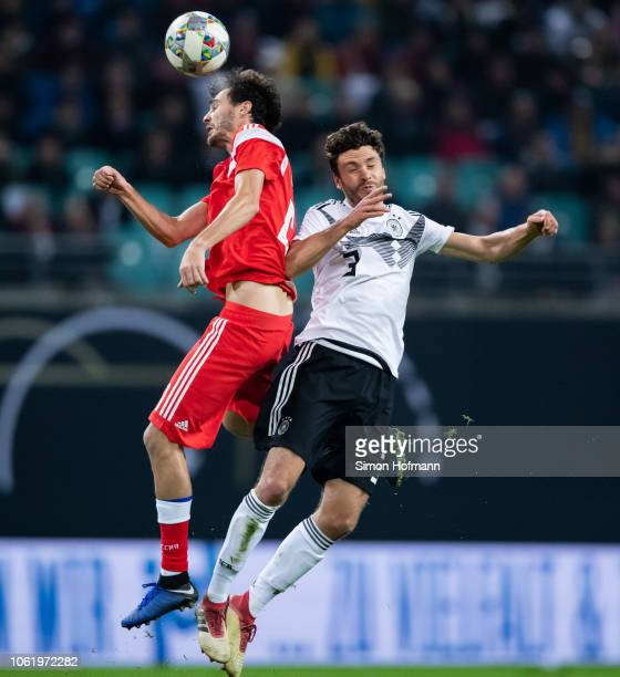 Jonas Hector of Germany jumps for a header with Aleksandr Erokhin of Russia during the International Friendly match between Germany and Russia at Red...