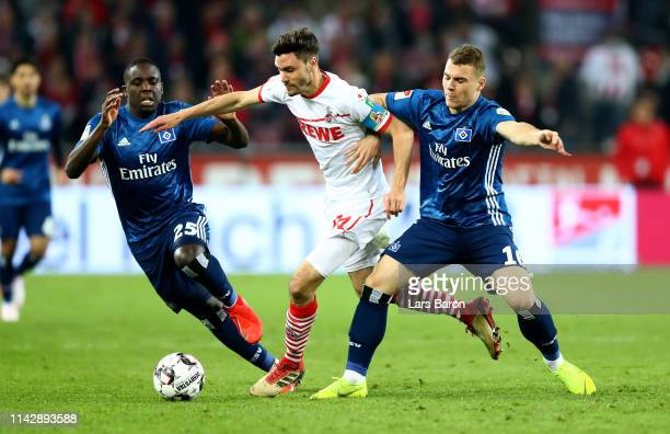 Jonas Hector of Koeln challenge Orel Mangala and Vasilije Janjicic of Hamburg during the Second Bundesliga match between 1 FC Koeln and Hamburger SV...