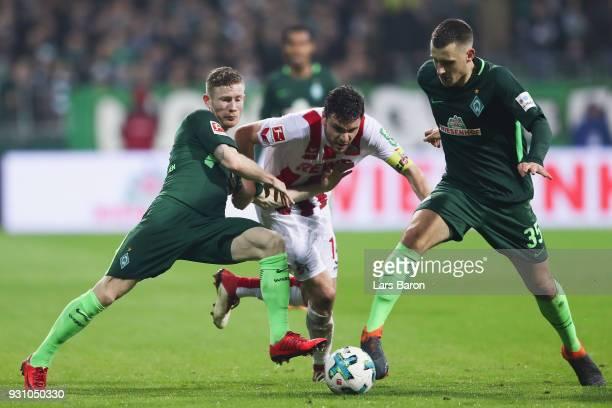 Jonas Hector of Koeln is challenged by Florian Kainz and Maximilian Eggestein of Bremen during the Bundesliga match between SV Werder Bremen and 1 FC...