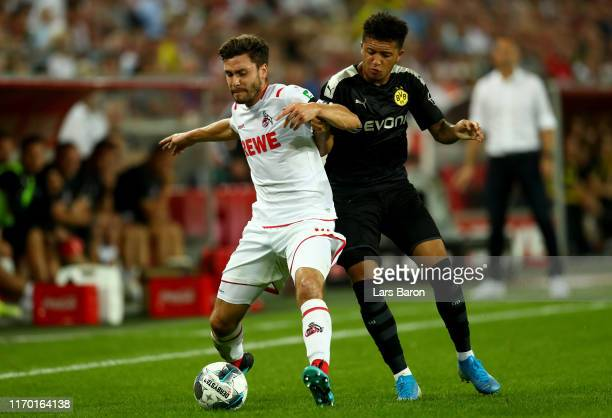 Jonas Hector of Koeln is challenged by Jadon Sancho of Dortmund during the Bundesliga match between 1. FC Koeln and Borussia Dortmund at...