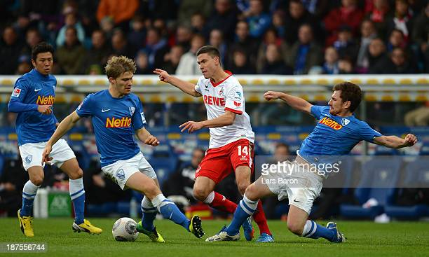 Jonas Hector of Koeln is challenged by Ken Ilsoe and Slawo Freier of Bochum during the Second Bundesliga match between VfL Bochum and 1 FC Koeln at...
