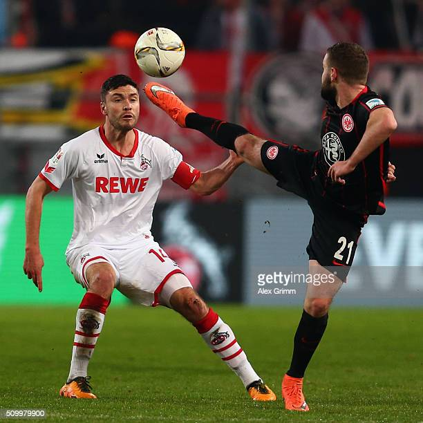 Jonas Hector of Koeln is challenged by Marc Stendera of Frankfurt during the Bundesliga match between 1 FC Koeln and Eintracht Frankfurt at...