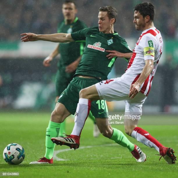 Jonas Hector of Koeln is challenged by Niklas Moisander of Bremen during the Bundesliga match between SV Werder Bremen and 1 FC Koeln at Weserstadion...