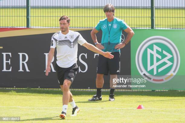 Jonas Hector runs next to Joachim Loew head coach of the German national team during a training session of the German national team at Sportanlage...
