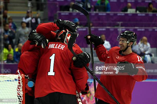 Jonas Hiller of Switzerland celebratse with his teammate Luca Cunti after defeating the Czech Republic 1 to 0 in the Men's Ice Hockey Preliminary...