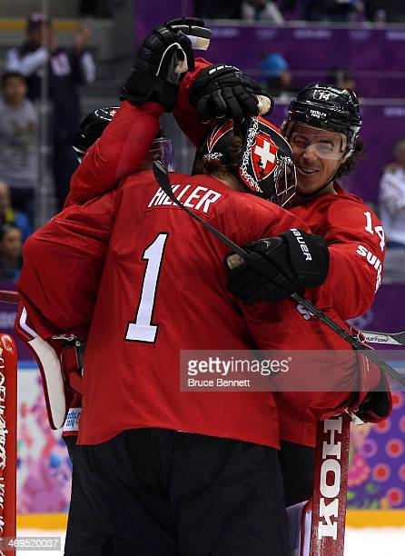 Jonas Hiller of Switzerland celebratse with his teammate Roman Wick after defeating the Czech Republic 1 to 0 in the Men's Ice Hockey Preliminary...
